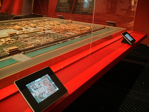 An iPad next to a scale model of a city
