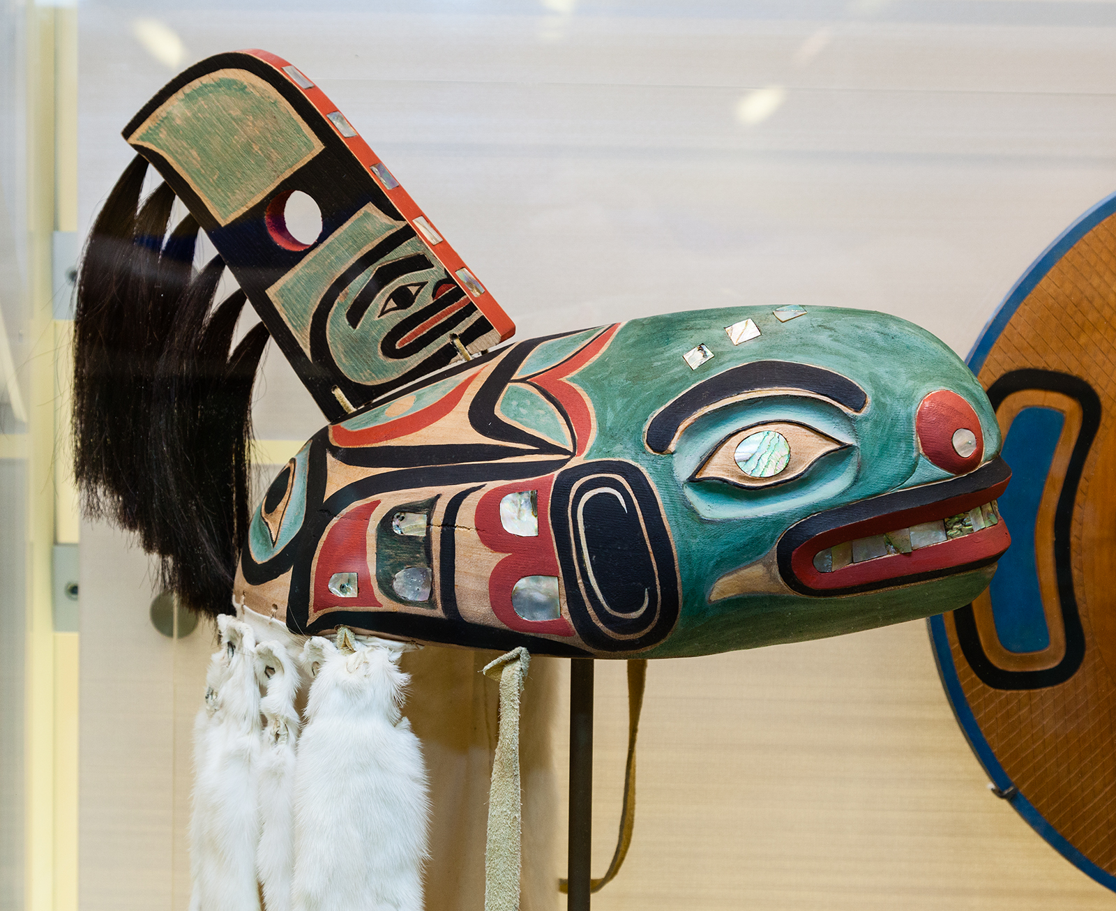 A replica of an original Tlingit, an Alaskan Native American tribe, Killer Whale hat, catalog number E433020, that is on display in Q?RIUS to help tell the story of the repatriation and the importance of clan hats to the Tlingit. The original hat, repatriated from the Smithsonian National Museum of Natural History, back to the clan in 2005.